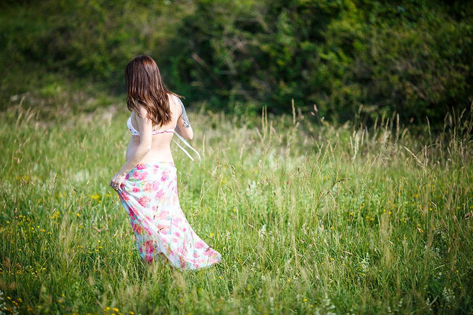 una embarazada andando por un prado en un reportaje de embarazo en irun