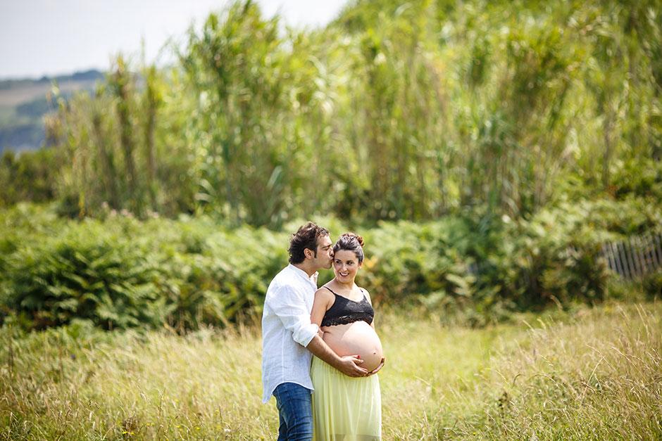 marido besando a su mujer en la frente en un embarazo