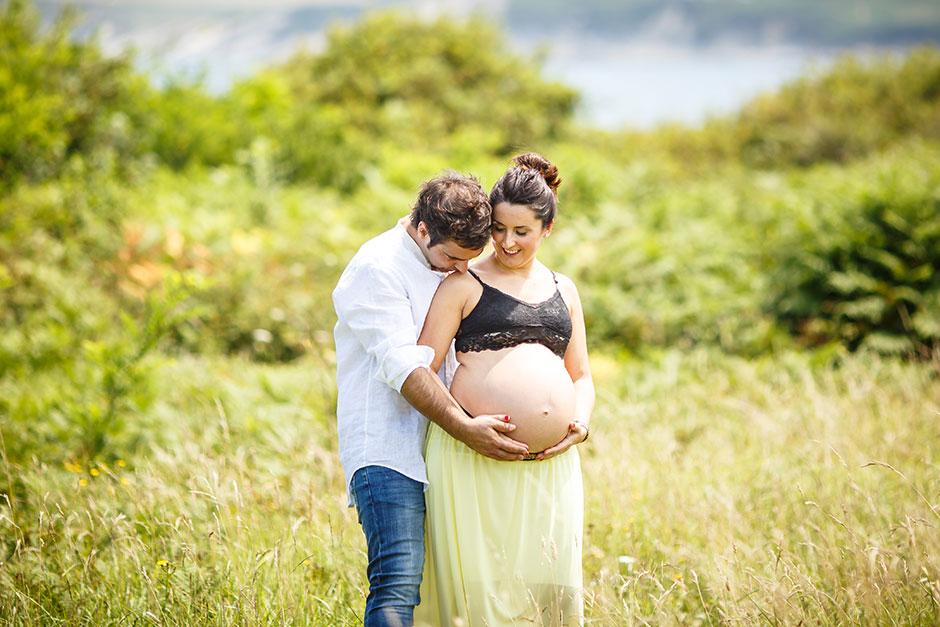 marido besando en el hombro a su mujer embarazada
