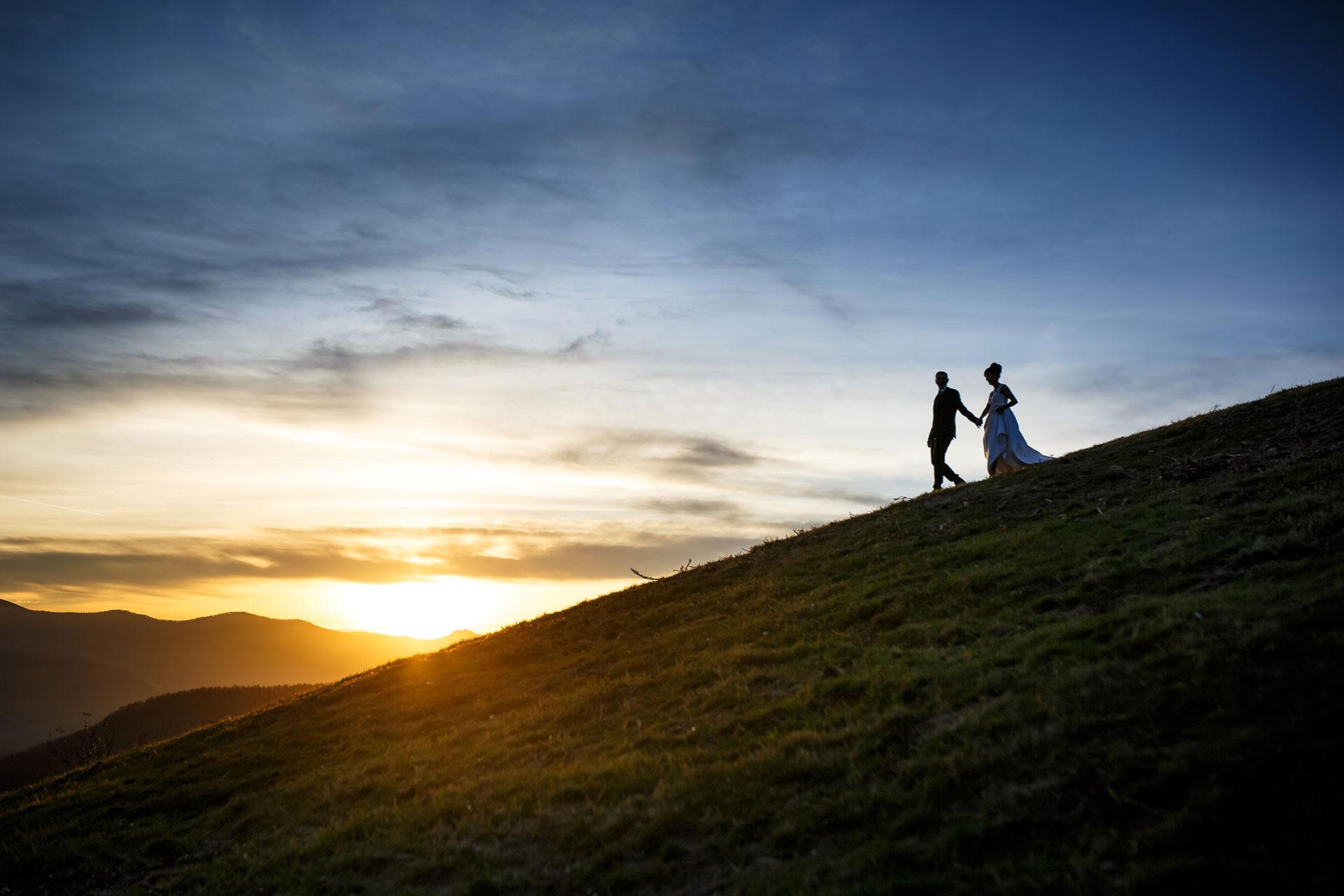 atardecer y una pareja bajando una ladera