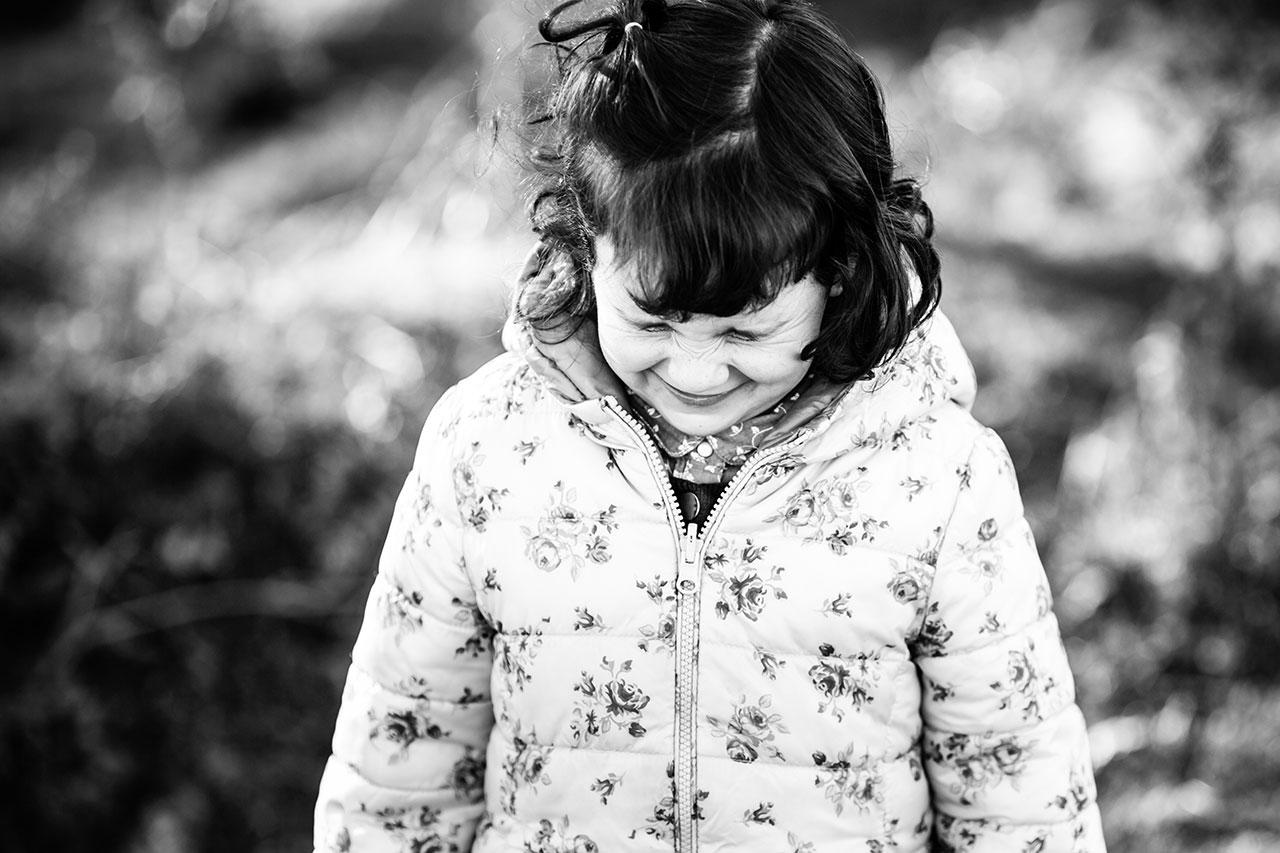 niña con los ojos cerrados fuerte en el reportaje de familia