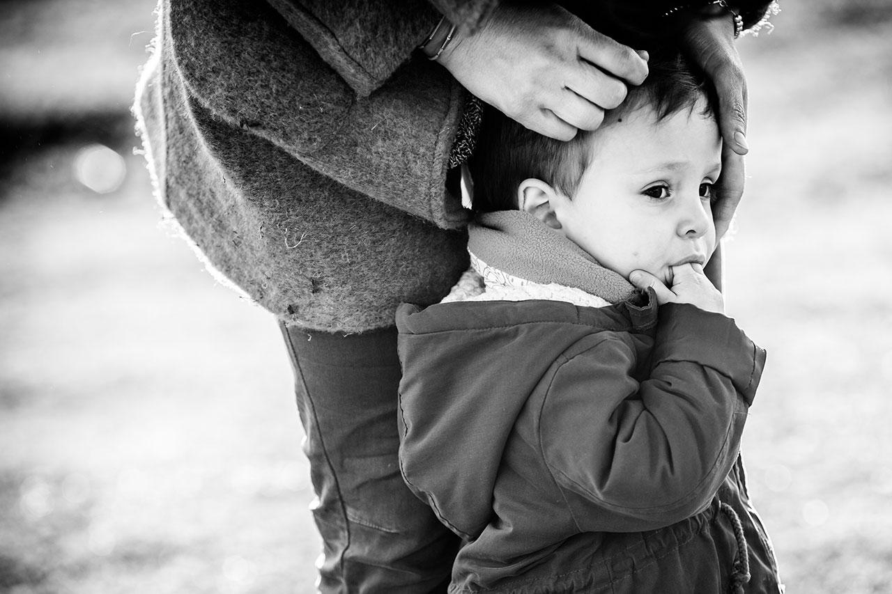 madre acariciando a su hijo y este chupandose los dedos en el reportaje de familia