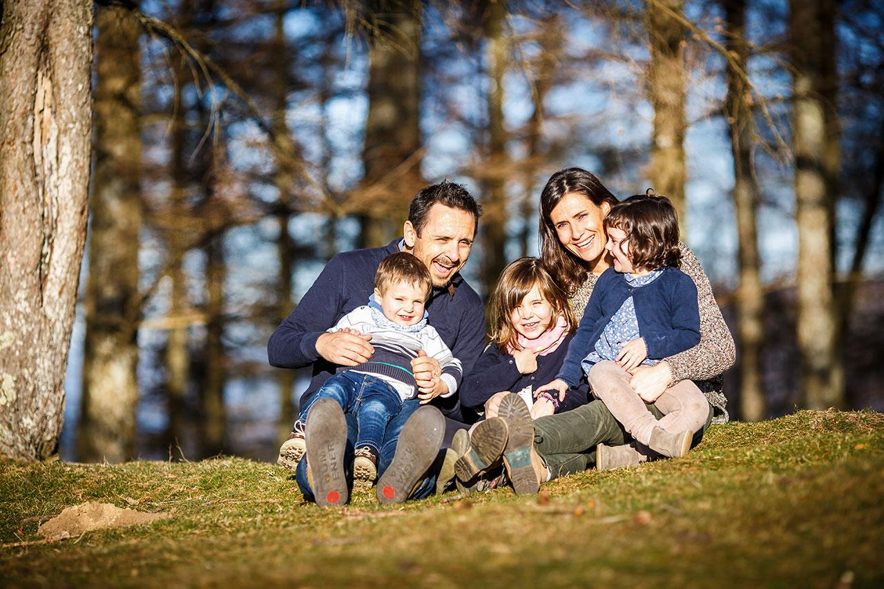 toda la familia sentada en el suelo en un reportaje de familia en peñas de aia