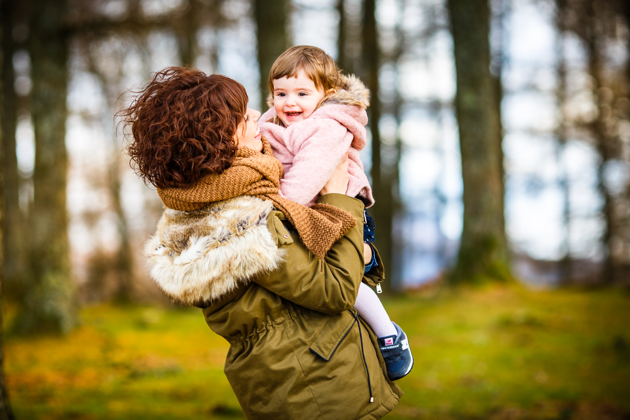 mama cogiendo en brazos a su pequeña en un reportaje de familia