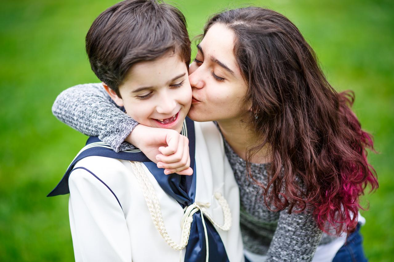 hermana besando a su hermano vestido de comunión en un reportaje de comunión