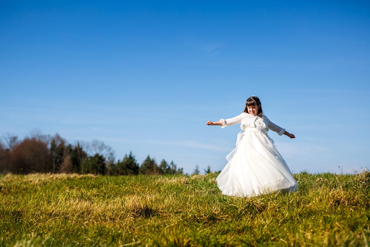niña dando vueltas en una pradera en un reportaje de comunión en san marcial