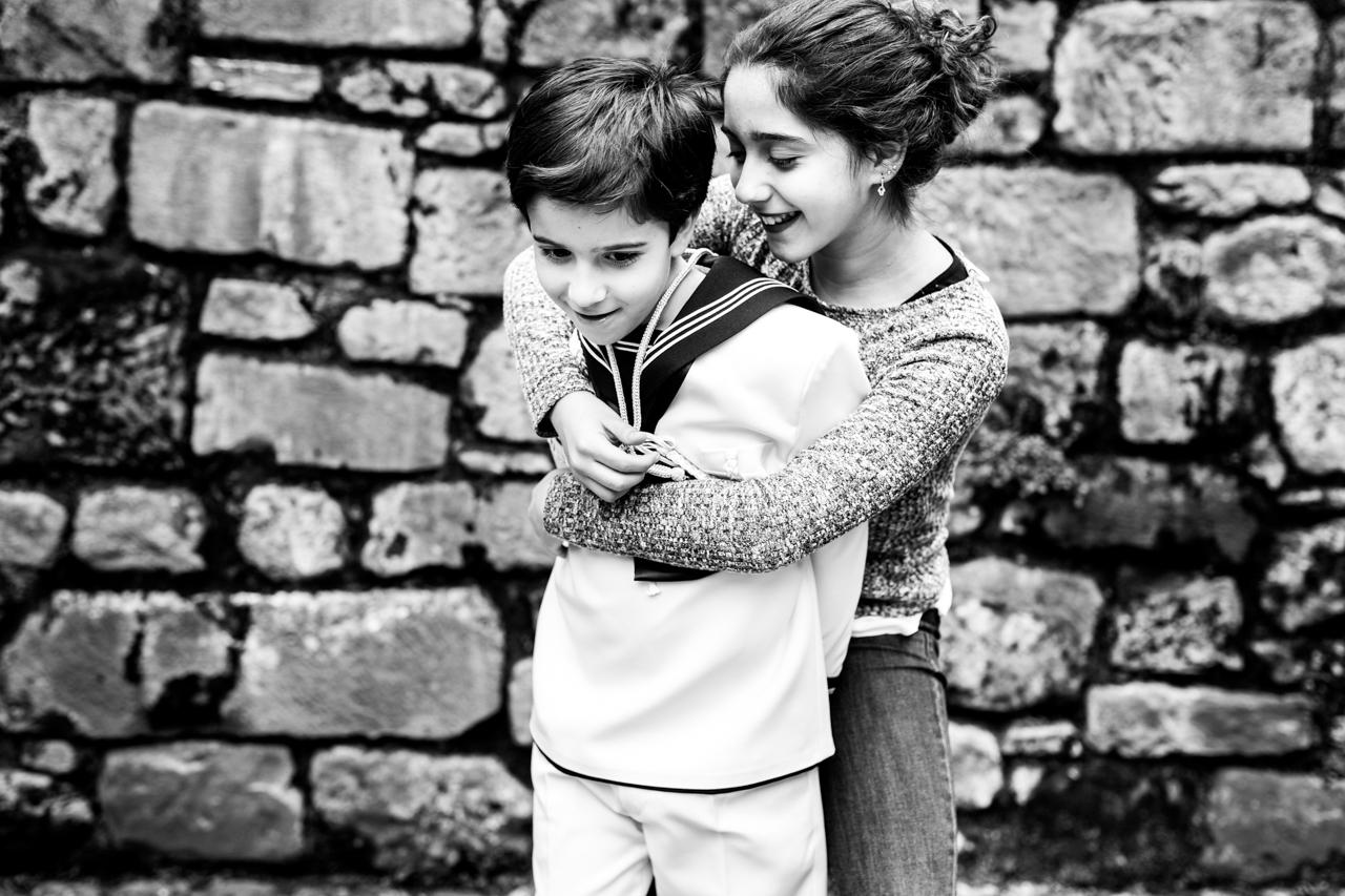hermana abrazando a su hermano vestido de comunión en un reportaje de comunión