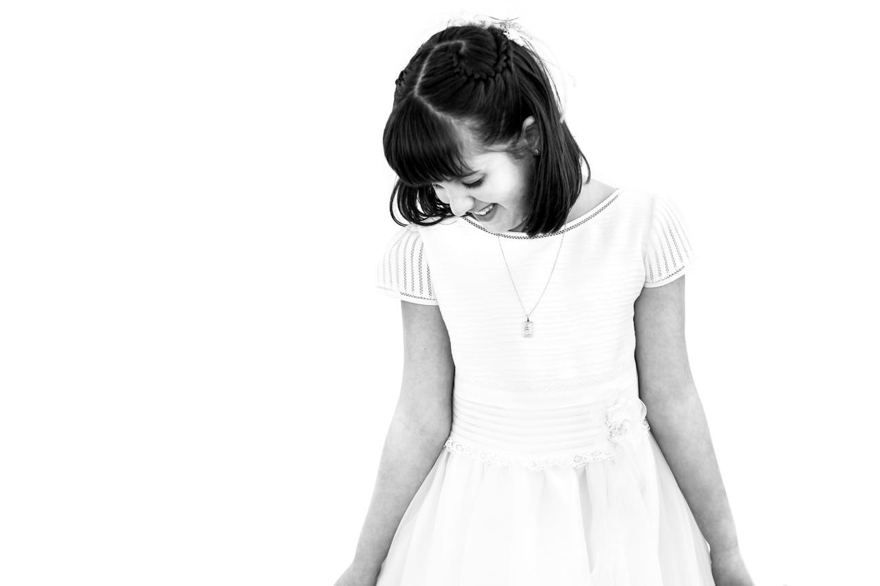 niña sonriendo en una pared blanca en un reportaje de comunión en san marcial