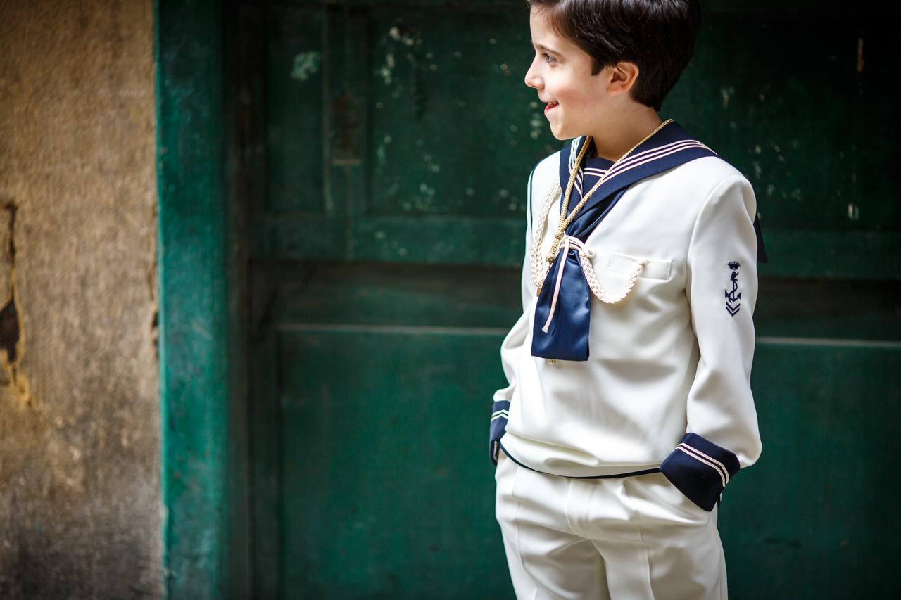 niño en una puerta verde en un reportaje de comunión en hondarribia