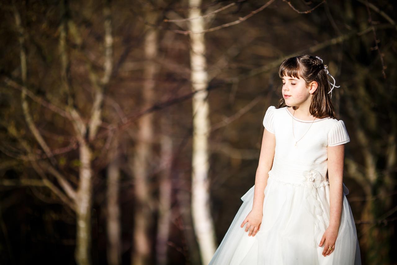 niña vestida de comunión dejandose llevar por el aire