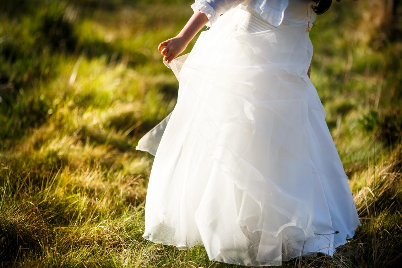 niña vestida de comunión agarrando el vestido