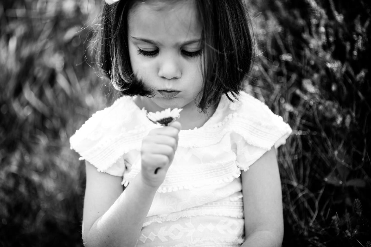 niña soplando una flor