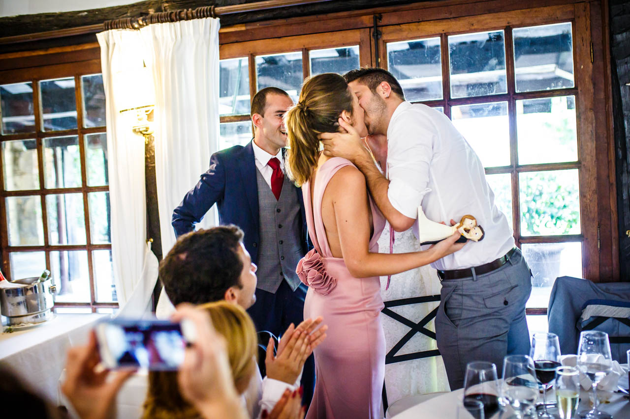 una pareja dándose un beso tras recibir los muñecos de la tarta en una boda en guadalupe