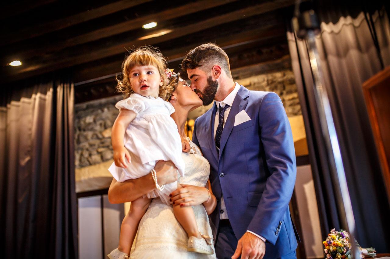 los novios besandose con la hija en una boda en oiartzun
