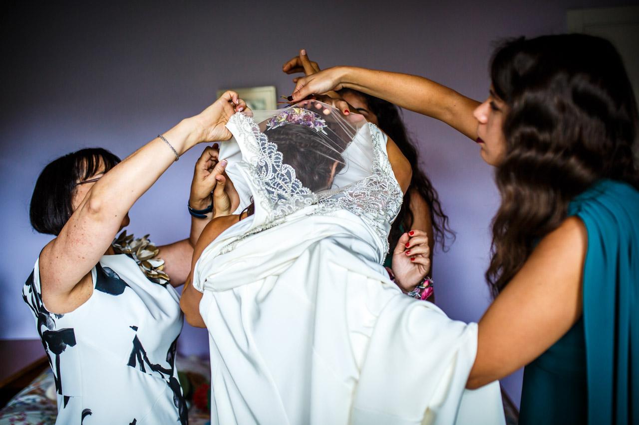 la madre de la novia y dos amigas le ponen el vestido a la novia en una boda en oiartzun