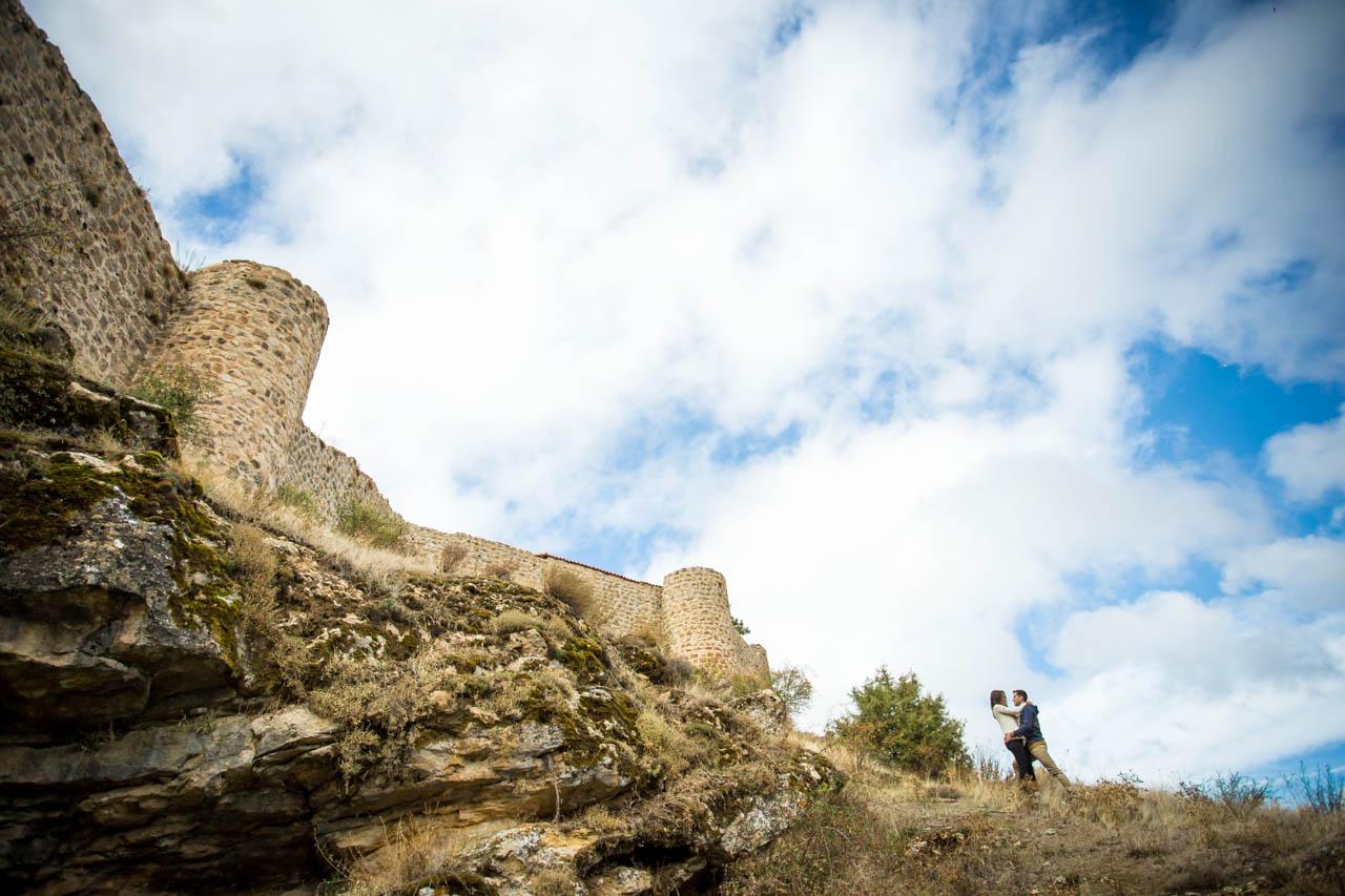 los novios abrazados junto a la muralla de Calatañazor en una preboda en Soria
