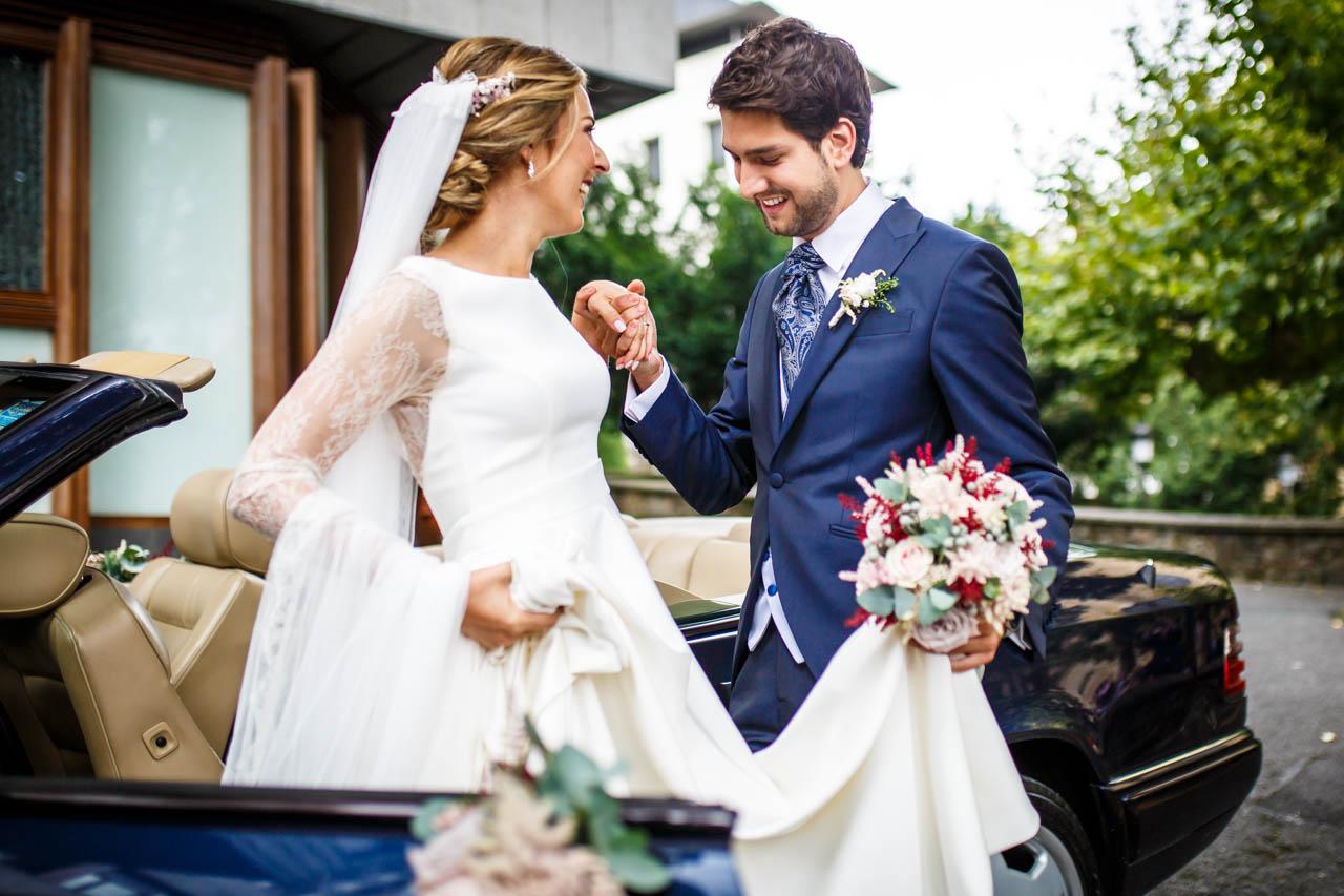 el novio ayuda a la novia ha salir del coche en una boda en irun