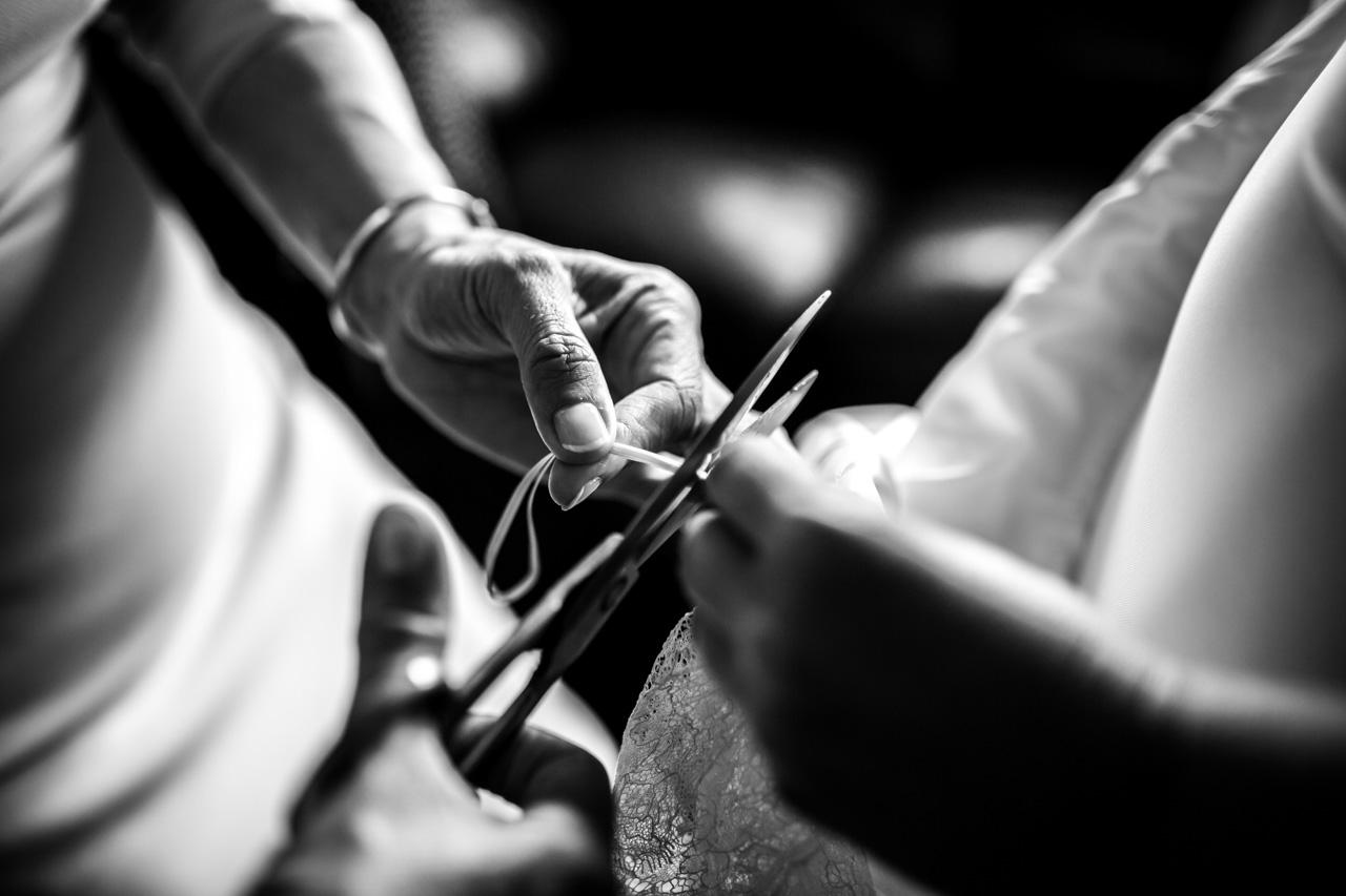 la madre de la novia cortando las tiras del vestido antes de ponérselo a la novia en una boda en irun