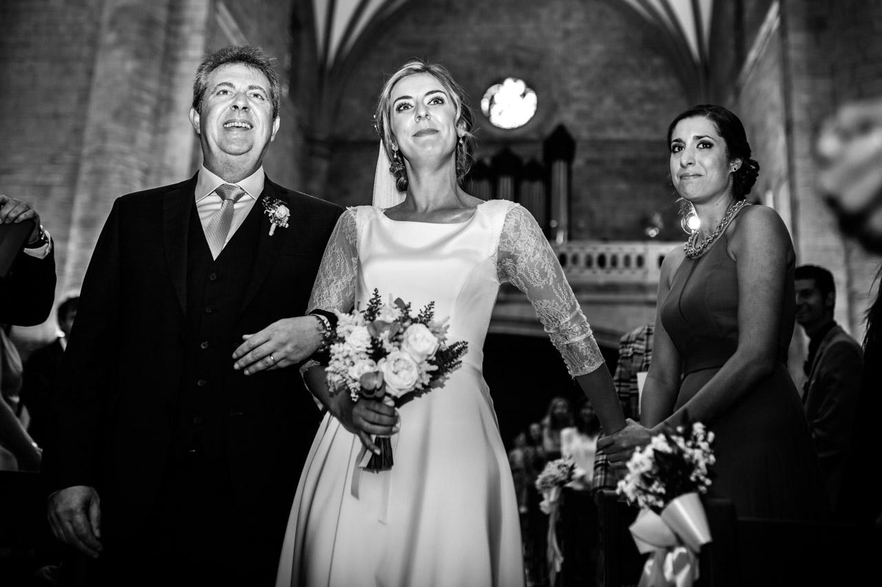 la novia le da la mano a su amiga emocionada mientras se dirige al altar junto con el padrino en una boda en irun
