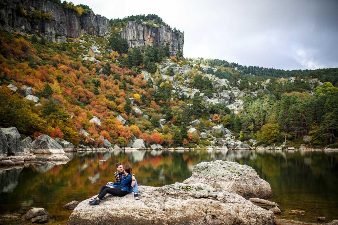 los novios hablan sentados en una roca de la laguna negra en una preboda en Soria