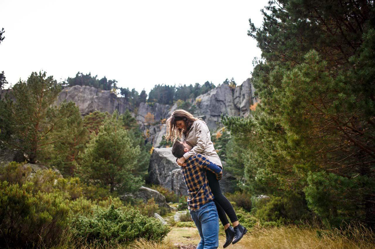El novio levanta a la novia en un abrazo en los alrededores de la laguna negra en una preboda en Soria