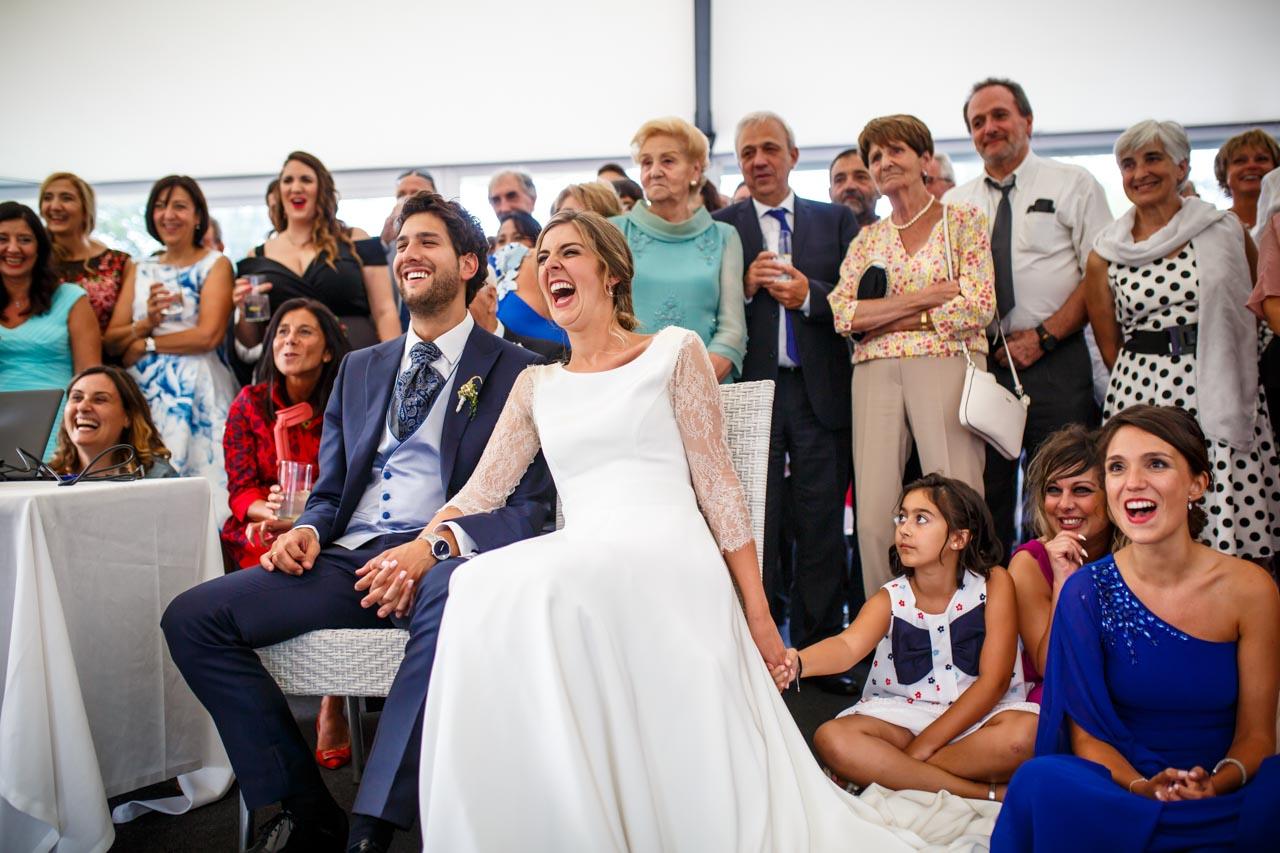 los novios y los invitados se ríen al ver un vídeo en una boda en el real club golf de san sebastian