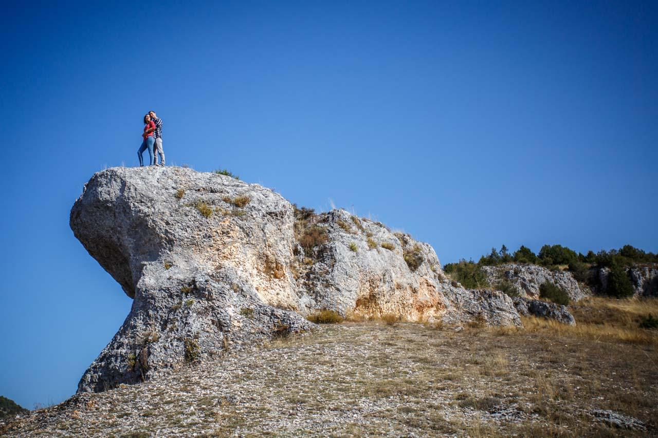 los novios miran al horizonte subidos a lo alto de una roca en una preboda en Soria