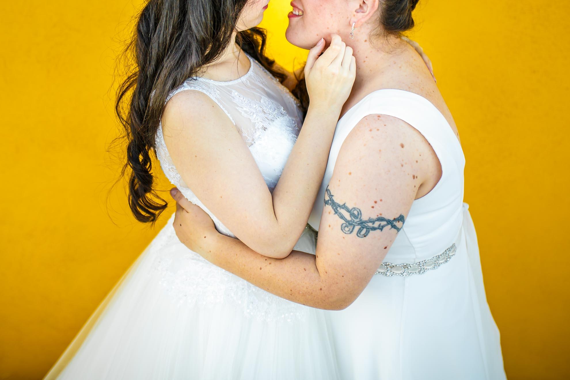 detalle de dos novias besandose sobre un fondo amarillo