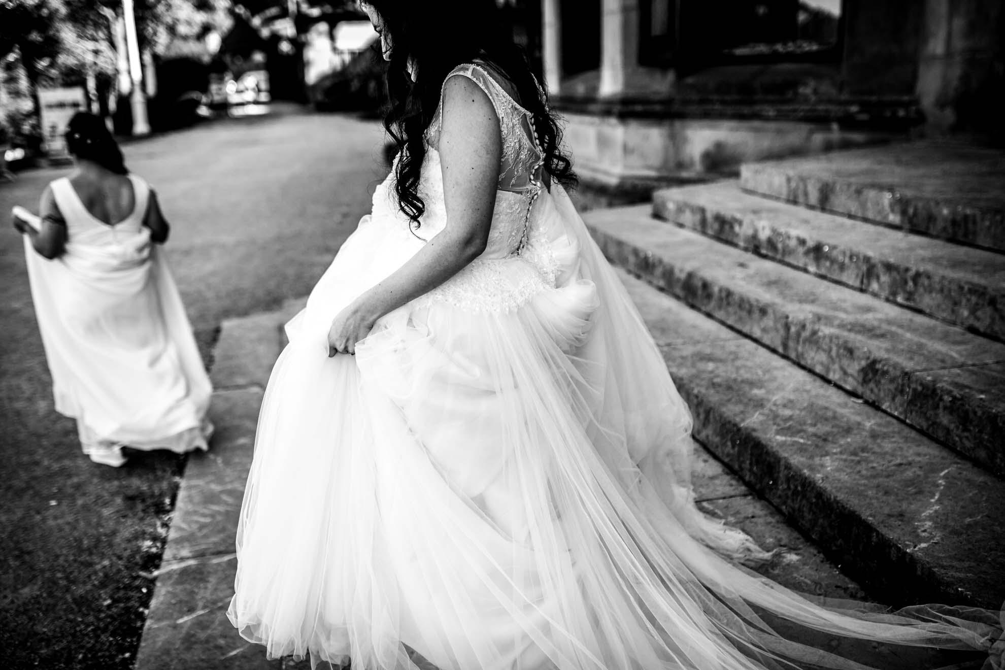 dos novias caminando por unas escaleras en blanco y negro