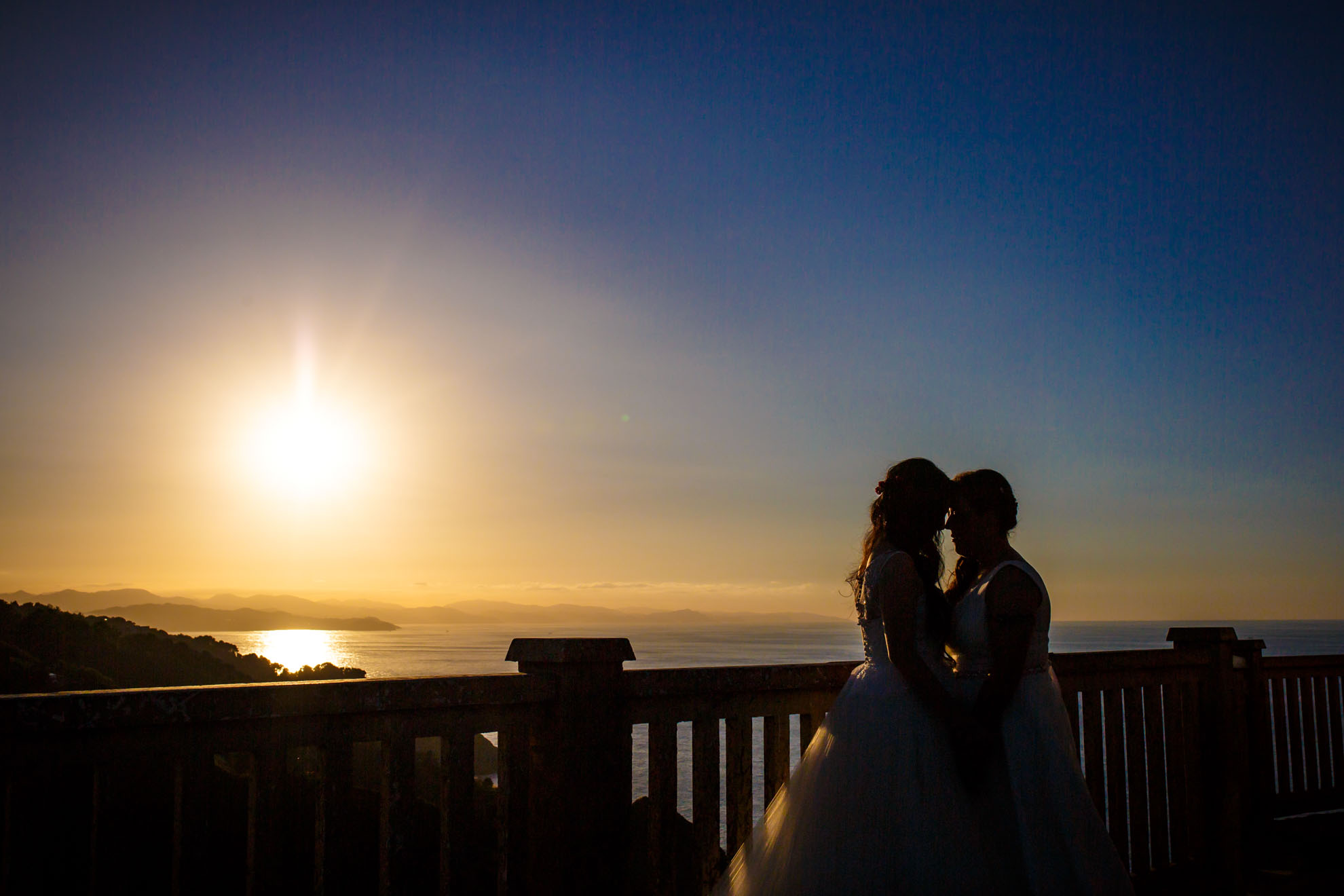 dos chicas caso besandose en un atardecer en el monte igeldo