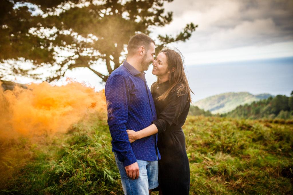 pareja de novios casi besandose fundida en humo naranja