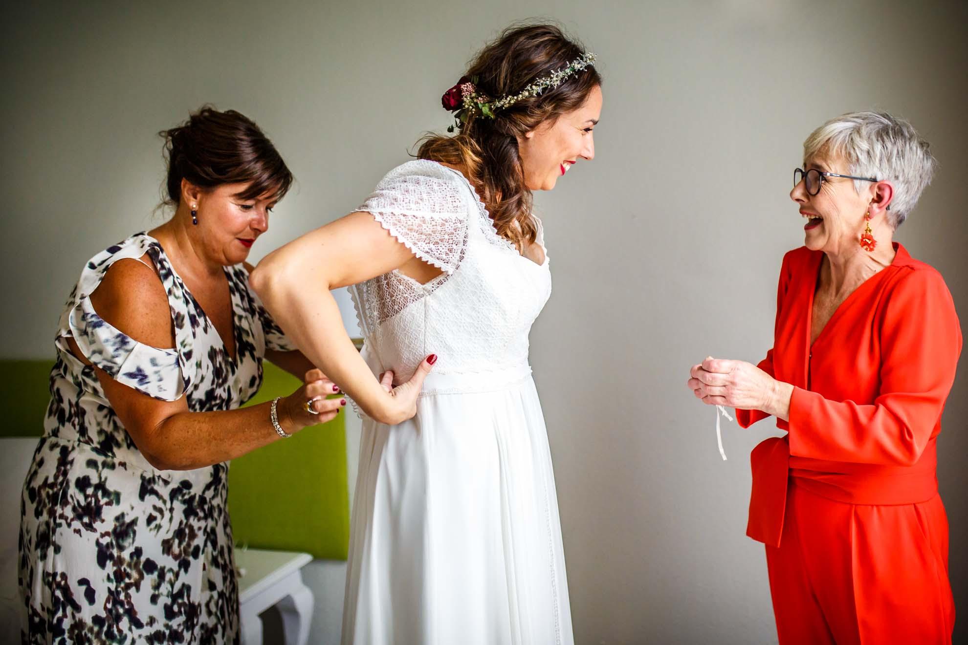 tia le abrocha el vestido mientras la novia se rie con su madre