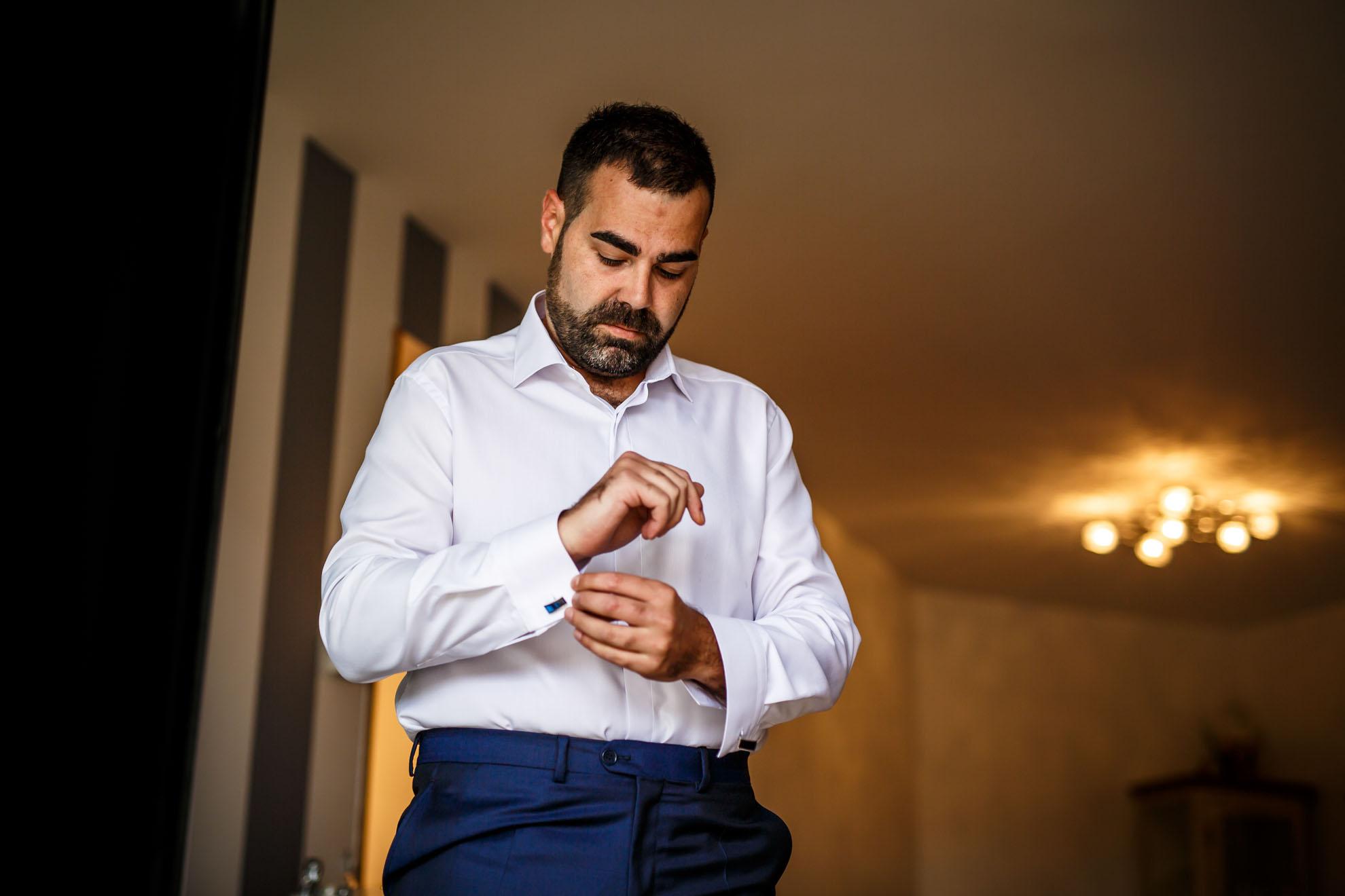 novio se ata el puño de la camisa