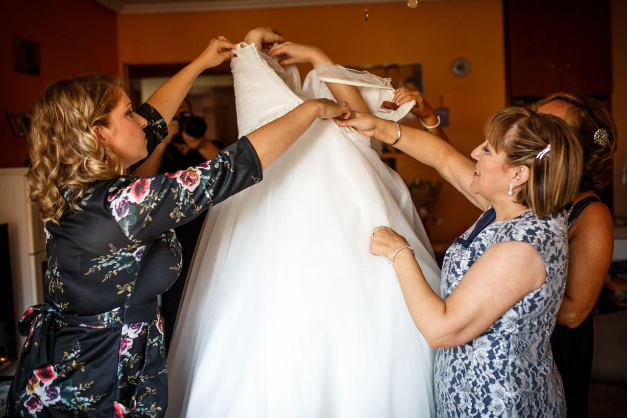 madre y dos amigas atando el vestido de la novia