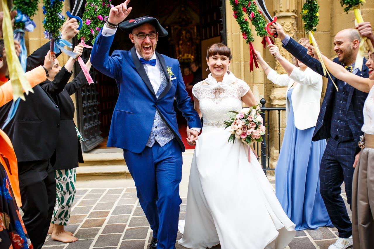 los novios felices cruzan el pasillo que hacen sus amigos en la salida de la iglesia en una boda en laguardia