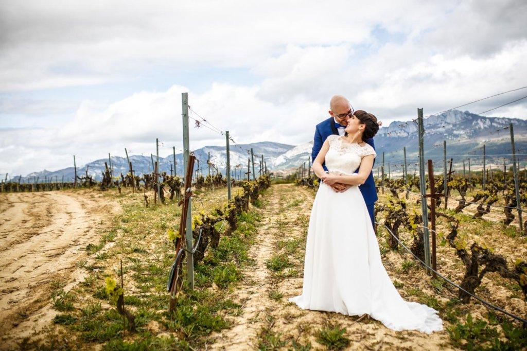 el novio abraza a la novia entre viñedos en una boda en laguardia