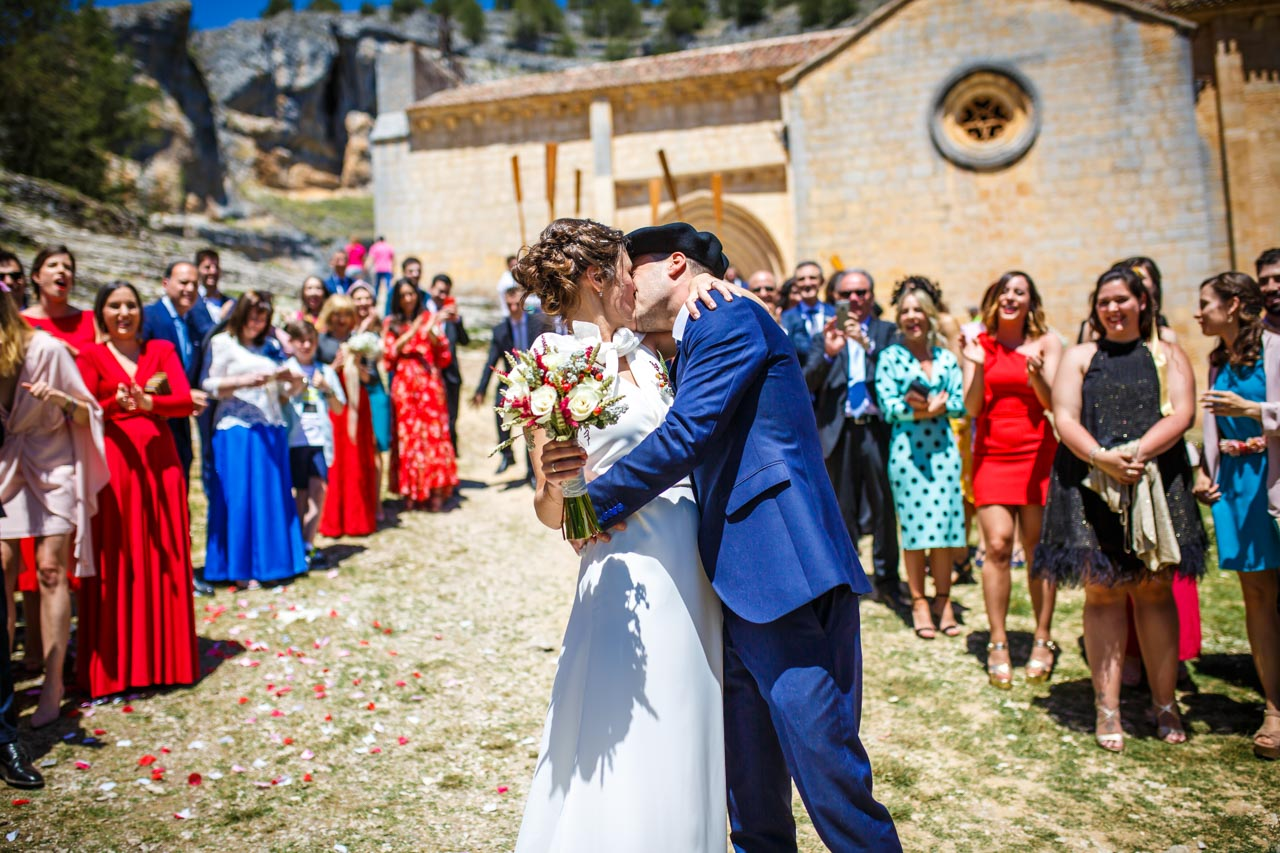 los novios se besan delante de todos los invitados al salir de la iglesia en una boda en soria