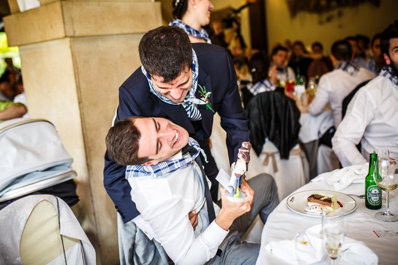 el novio abraza a su amigo mientras le entrega los muñecos de la tarta en una boda en bekoerrota