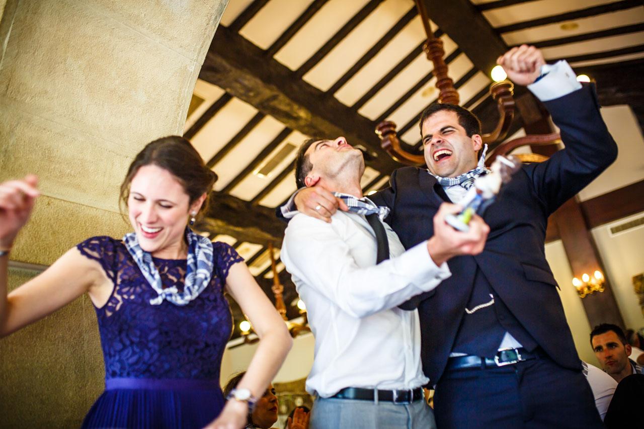 el novio bailando con un amigo tras entregarle los muñecos de la tarta en una boda en bekoerrota