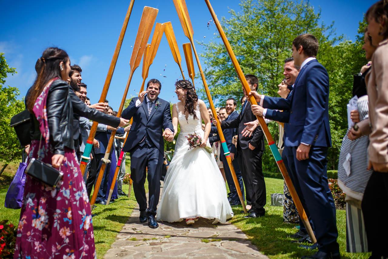 los novios atraviesan un arco hecho con remos por sus amigos en una boda en bekoerrota