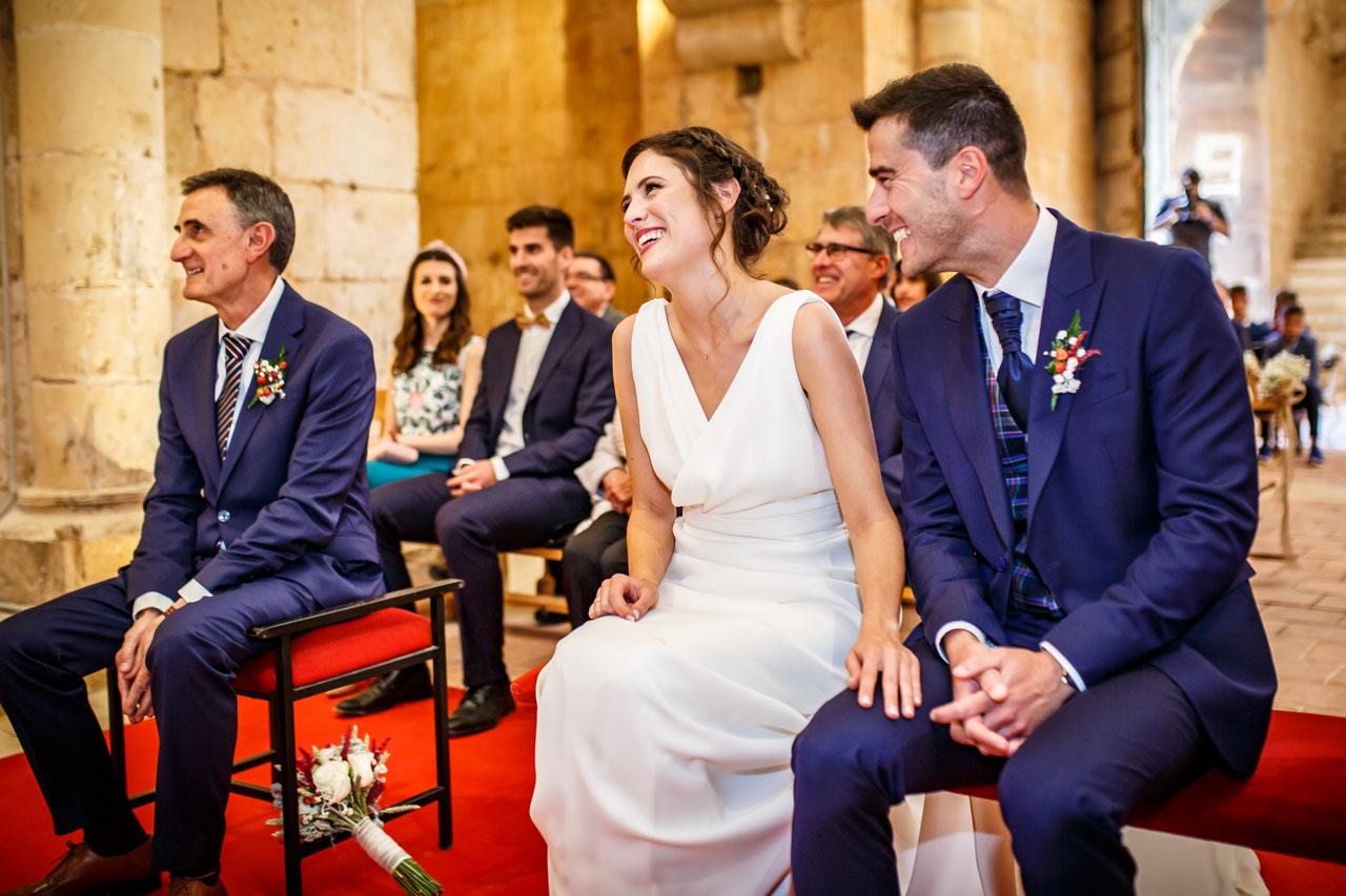 los novios se ríen mientras sus amigos leen en la ceremonia en una boda en soria
