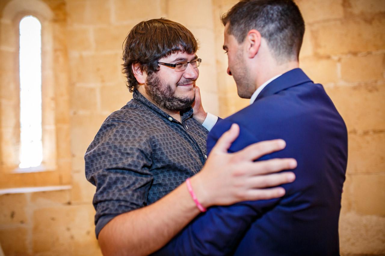 un amigo del novio se abraza con él después de leer en una boda en soria