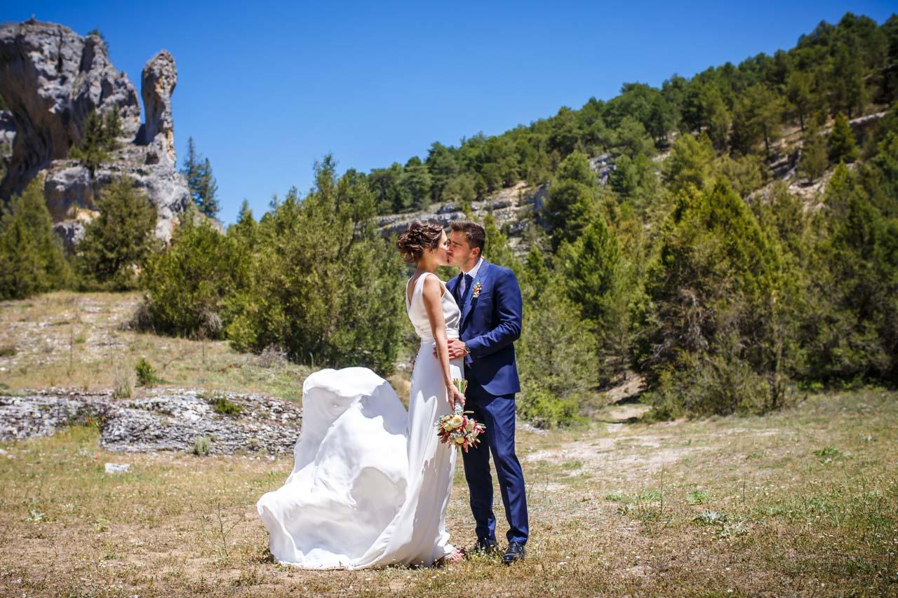 los novios se besan durante el reportaje en el cañón de río lobos en una boda en soria