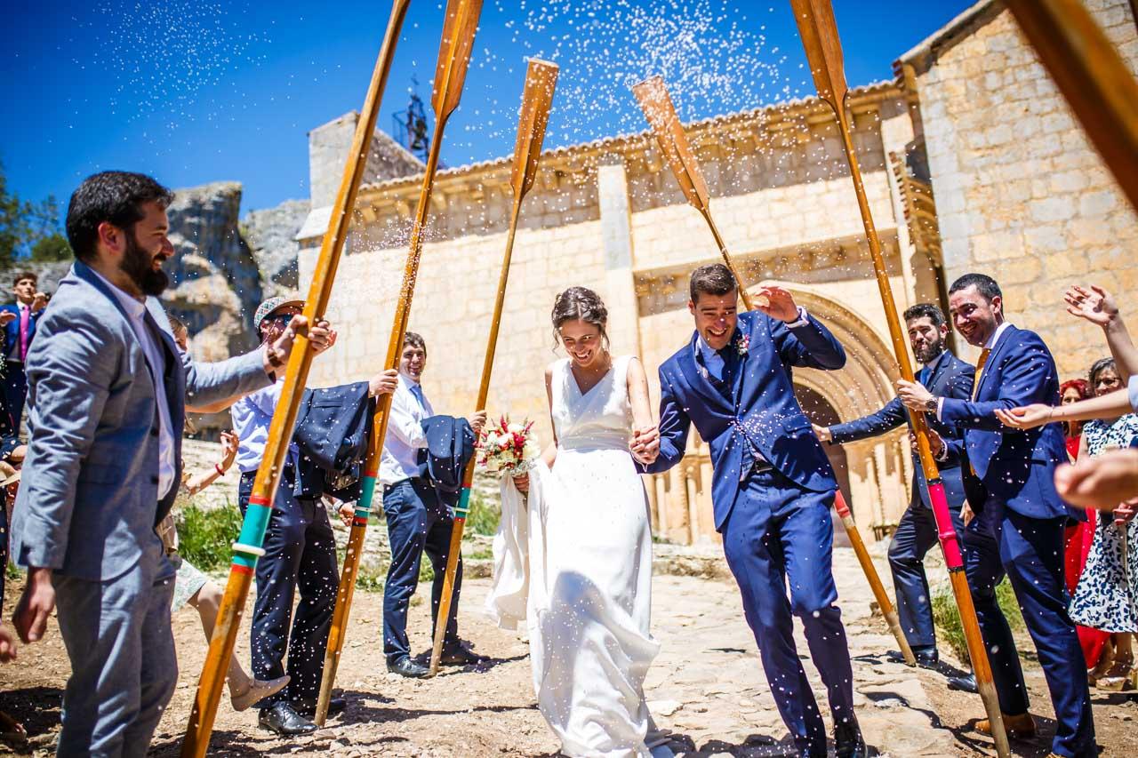 los novios saliendo de la iglesia pasando por el arco de remos que les hacen los amigos en una boda en soria