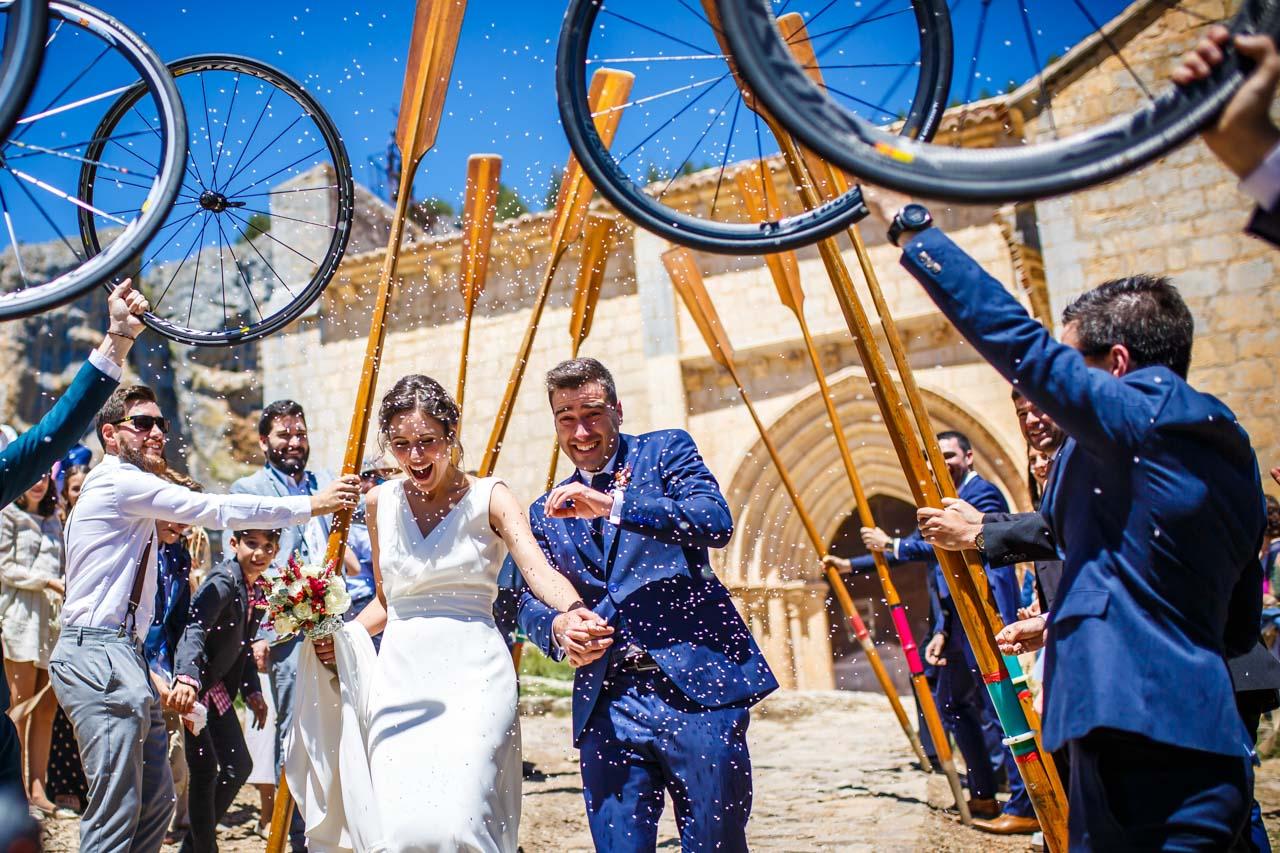 los novios pasan por un arco hecho con remos y ruedas de bici en una boda en soria