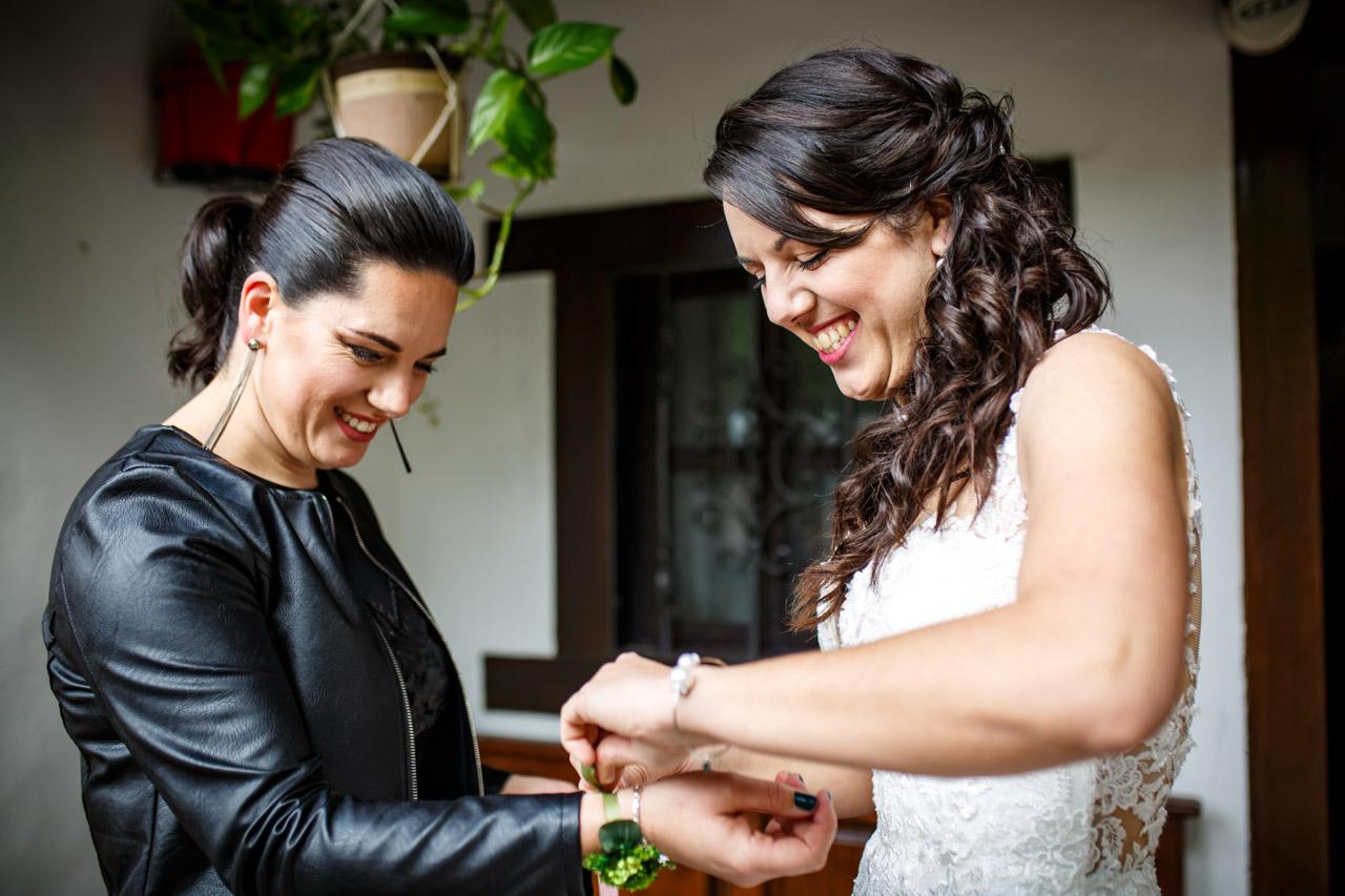 la novia atando una pulsera a su otra hermana en una boda en bekoerrota