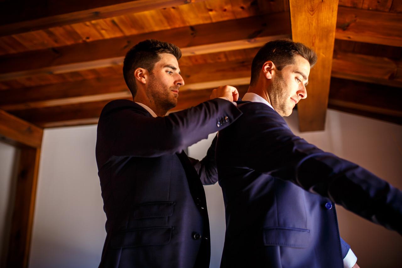 el novio se pone la chaqueta con la ayuda de su hermano en una boda en soria