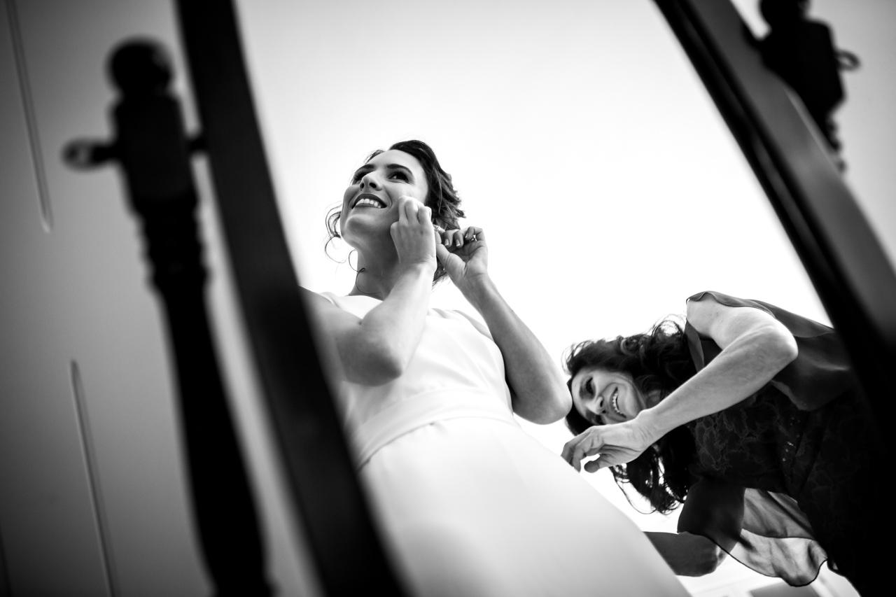 la madre ajusta el vestido a la novia, mientras esta se pone los pendientes en una boda en soria