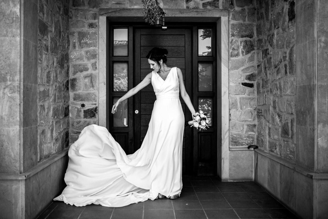 la novia se coloca bien el vestido en la entrada de su casa en una boda en soria