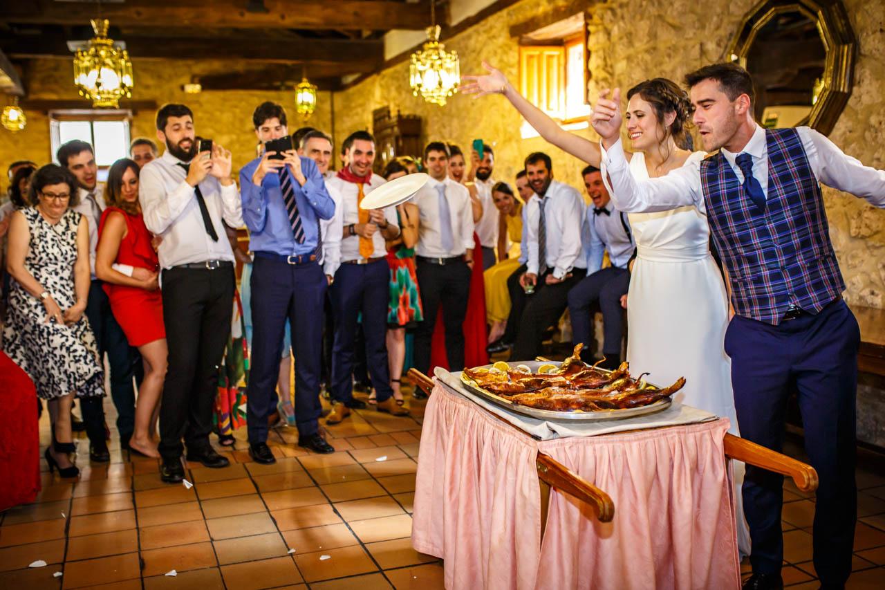 los novios lanzan el plato después de cortar el cochinillo con él en una boda en soria